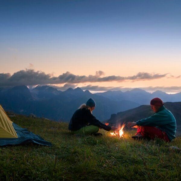 Tina Eckert sitzt mit einem Mann am Lagerfeuer