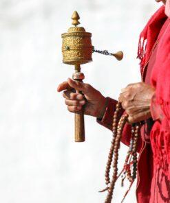 Mönch hält Gebetsmühle und Mala in der Hand