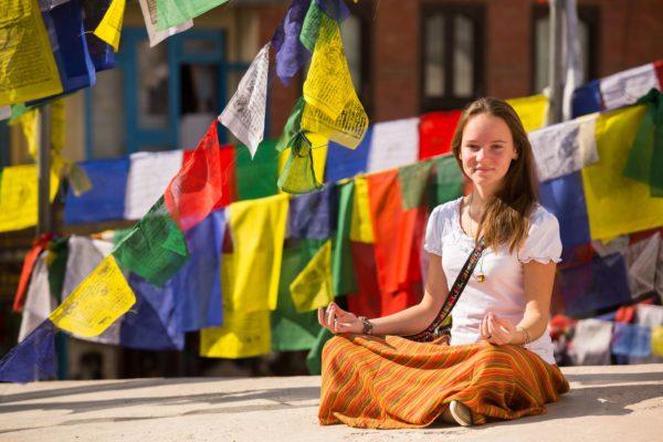 Mädchen meditiert in Nepal und ist von Gebetsfahnen umgeben